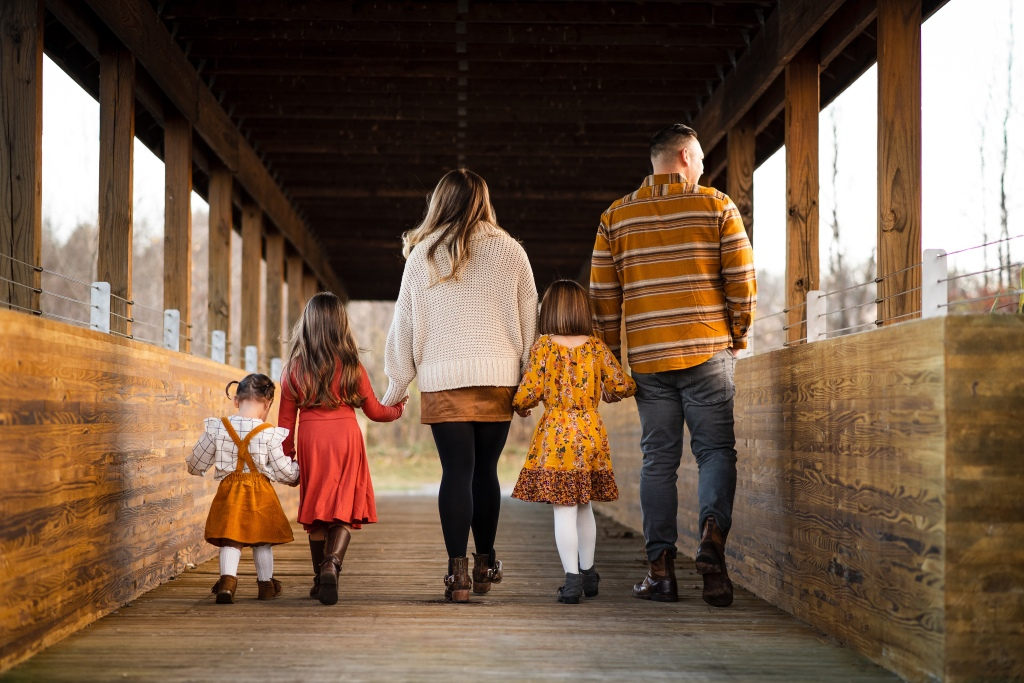 A family holding hands walking away from the camera over a bridge